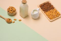 Almond oil in bottle and milk with almonds on black wooden table.  Royalty Free Stock Image