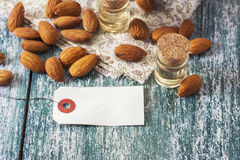 Almond oil in bottle  and nuts on wooden background Stock Photos