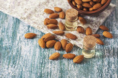 Almond oil in bottle  and nuts on wooden background Stock Images