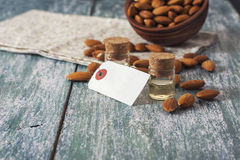 Almond oil in bottle  and nuts on wooden background Royalty Free Stock Image