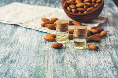 Almond oil in bottle  and nuts on wooden background Royalty Free Stock Photos