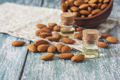 Almond oil in bottle  and nuts on wooden background Royalty Free Stock Images