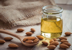 Almond oil in glass bottle and almonds on wooden table. Almond oil in glass bottle and almonds on a wooden table Royalty Free Stock Images