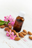 Almond oil in a small bottle and scattered almonds nuts and flow Stock Photo