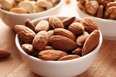 Almond and other nuts in white bowls Stock Photos