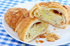 Almond Pastry. A almond danish pastry, sliced, on a white plate Stock Photos
