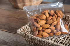 Almond in plastic bag on basket. Stock Images