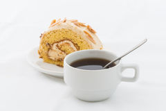 Almond roll cake on white dish with hot drink Stock Image
