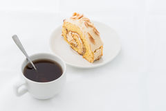Almond roll cake on white dish with hot drink Stock Photos