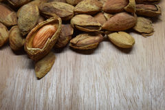 Almond space for text. Pile of dry almond nuts spread out on wooden surface and empty space for text Stock Image