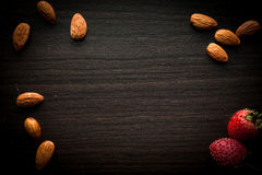 Almond and strawberries wood background Stock Photo