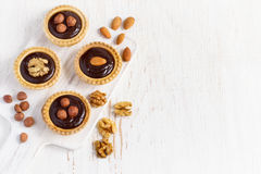 Almond walnut hazelnut chocolate small tarts on a white backgrou Stock Image