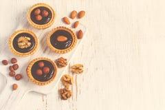 Almond walnut hazelnut chocolate small tarts on a white backgrou Royalty Free Stock Photo
