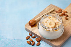 Almond yogurt with banana. Honey in a glass jar on a blue background stock images