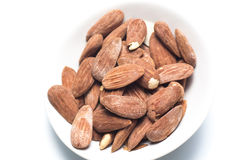 Almonds. White dish of salted and toasted almonds on a white background Stock Images