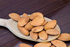 Almonds. Closeup of almonds over a wooden spoon Stock Images