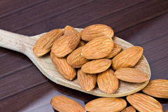 Almonds. Closeup of almonds over a wooden spoon Stock Image