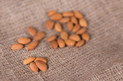 Almonds. On sackcloth close up on blurred background Royalty Free Stock Photo