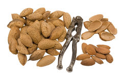 Almonds. Several whole and shelled almonds with nutcracker against white background royalty free stock photography