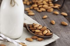 Almonds with Almond Milk. Whole almonds in a wooden spoon over a rustic table with a glass bottle of almond. Extreme shallow depth of field with selective focus Stock Photos