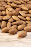 Almonds Almond Nuts Food. Raw almonds spilling forwardl onto a wood surface Royalty Free Stock Photos