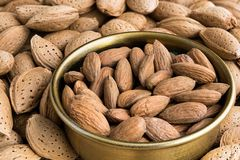 Almonds. Peeled in a bowl or in their nutshell Stock Images