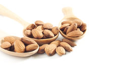 Almonds, almonds on wooden spoon isolated over white background. Selective focus at front Royalty Free Stock Photos