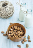 Almonds in a bamboo bowl with almond milk in bottles Royalty Free Stock Photo