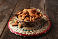 Almonds in basket on brown wooden background Royalty Free Stock Photography
