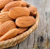 Almonds in the basket on old wood background Royalty Free Stock Images