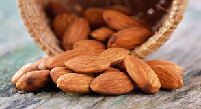 Almonds in the basket on old wood background Stock Image