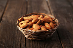 Almonds in basket on wooden background Stock Images