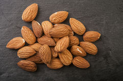 Almonds in a black plate. Royalty Free Stock Photo