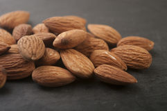 Almonds in a black plate. Stock Image
