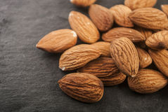 Almonds in a black plate. Stock Photography