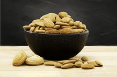 Almonds in black porcelain bowl on wooden table stock photography