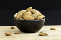 Almonds in black porcelain bowl on wooden table with unfocused background. Almonds and nuts in black porcelain bowl on wooden table with unfocused background stock image