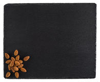 Almonds on a black slate board. Isolated on white background. Royalty Free Stock Images