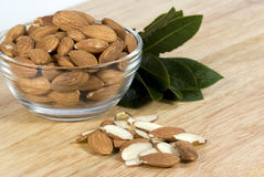 Almonds in Bowl. Fresh raw almonds in glass bowl on wood cutting board Stock Photos