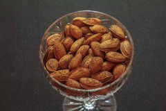 Almonds. In a bowl on a dark gray background Stock Images