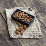 Almonds in  bowl on grained wood background Royalty Free Stock Photos