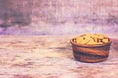 Almonds in a bowl on the old wooden background. Stock Photos