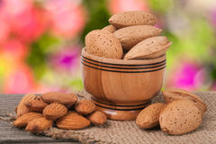 Almonds in a bowl on the old wooden board blurred garden background Stock Photography