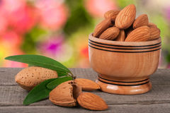 Almonds in a bowl on the old wooden board with blurred garden background Stock Photos