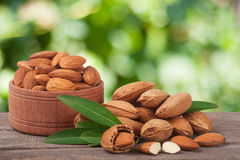 Almonds in a bowl on the old wooden board with blurred garden background Royalty Free Stock Images