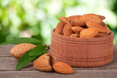 Almonds in a bowl on the old wooden board with blurred garden background Stock Photo
