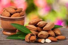 Almonds in a bowl on the old wooden board with blurred garden background Royalty Free Stock Photos