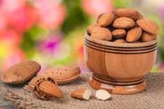 Almonds in a bowl on the old wooden board with sackcloth and blurred garden background Royalty Free Stock Photography
