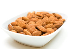 Almonds in bowl over white background Stock Photo