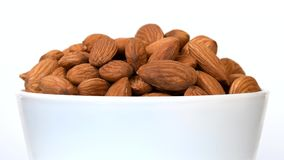 Almonds in bowl rotating close-up on white. Background stock video footage